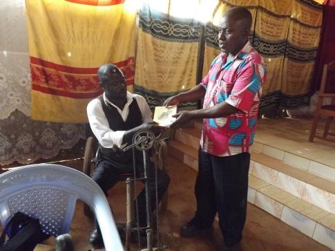 Donatien Ibassa remettant un guide imagé recensant les droits des PVH à un bénéficiaire